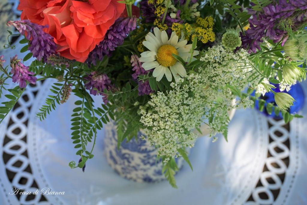 Fiori di campo su tavola apparecchiata in giardino con piatti bianchi e blu a casa di Bianca