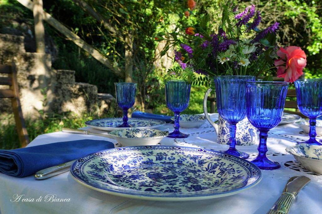 Tavola apparecchiata in giardino con piatti bianchi e blu